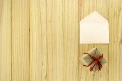 Τοπ άποψη του κιβωτίου δώρων τεχνών με το φάκελο στο ξύλο Στοκ Φωτογραφία