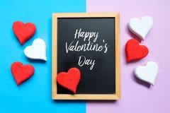 Τοπ άποψη του κόκκινων και άσπρων ξύλινων handcraft και του πίνακα καρδιών που γράφονται με ευτυχές Valentine& x27 ημέρα του s στ Στοκ Εικόνες