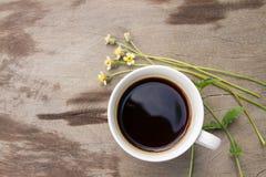 Τοπ άποψη του μαύρου καφέ σε ένα άσπρο φλυτζάνι με το λουλούδι χλόης σε ξύλινο Στοκ Εικόνα