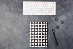 Τοπ άποψη του μαύρου υποβάθρου γραφείων γραφείων διαστήματος εργασίας με το σημειωματάριο εγγράφου copybook, το πληκτρολόγιο, τη  στοκ εικόνα