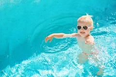 Τοπ άποψη του μικρού κοριτσιού που κολυμπά στη λίμνη με το μπλε νερό στοκ εικόνες