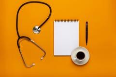 Τοπ άποψη του πίνακα γραφείων γιατρών με το στηθοσκόπιο, τον καφέ και το κενό έγγραφο για την περιοχή αποκομμάτων με τη μάνδρα Η  στοκ εικόνες με δικαίωμα ελεύθερης χρήσης