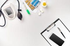 Τοπ άποψη του πίνακα γραφείων γιατρών ` s, κενό έγγραφο στην περιοχή αποκομμάτων με τη μάνδρα, ηλεκτρονικό μανόμετρο για να μετρή Στοκ Εικόνες