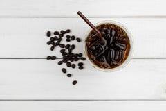 Τοπ άποψη του παγωμένων μαύρων καφέ και των φασολιών καφέ στο ξύλινο BA whie στοκ φωτογραφίες
