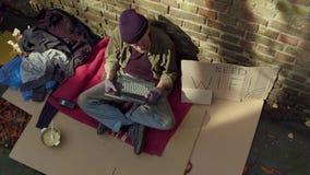 Τοπ άποψη του παλαιού άστεγου lap-top εκμετάλλευσης ατόμων στα χέρια φιλμ μικρού μήκους