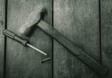 Τοπ άποψη του παλαιών σφυριού, του κατσαβιδιού και του καρφιού στον παλαιό ξύλινο πίνακα Εργαλεία ξυλουργικής για την αποτύπωση κ στοκ φωτογραφία με δικαίωμα ελεύθερης χρήσης