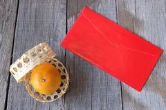 Τοπ άποψη του πορτοκαλιού σε ένα καλάθι στον παλαιό ξύλινο πίνακα με το κινεζικό κόκκινο πακέτο φακέλων ή το υπόβαθρο pao ANG κιν Στοκ Εικόνες