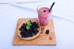 Τοπ άποψη του ποτού μούρων με τη φρέσκια μέντα σε ένα μπλε υπόβαθρο υφασμάτων Ένα ξύλινο πιάτο με τα βατόμουρα σε ένα τέμνον γραφ Στοκ εικόνα με δικαίωμα ελεύθερης χρήσης