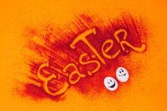 Τοπ άποψη του σημαδιού Πάσχας φιαγμένη από κόκκινη άμμο με τα αυγά κοτόπουλου με τα smileys Στοκ εικόνα με δικαίωμα ελεύθερης χρήσης