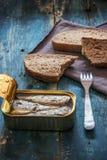 Τοπ άποψη του σπιτικού ολόκληρου ψωμιού σιταριού και των κονσερβοποιημένων ψαριών στον αγροτικό πίνακα στοκ εικόνα