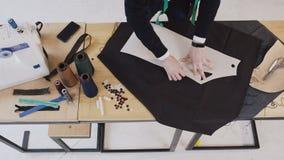 Τοπ άποψη του σχεδιαστή μόδας ή του ράφτη που κάνει ένα σχέδιο σε ένα καφετί κομμάτι του ιστού Η μοδίστρα χρησιμοποιεί μια κιμωλί φιλμ μικρού μήκους