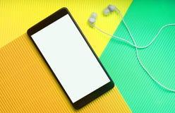 Τοπ άποψη του τηλεφώνου κυττάρων με τα ακουστικά στο καθιερώνον τη μόδα πολύχρωμο δονούμενο υπόβαθρο στοκ φωτογραφία