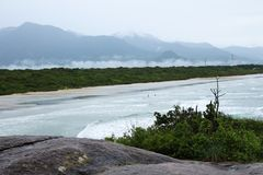 Τοπ άποψη του τοπίου με τους ανθρώπους που περπατούν μεταξύ της άμμου και των κυμάτων της θάλασσας και τα βουνά στο υπόβαθρο στοκ φωτογραφία