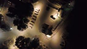 Τοπ άποψη του υπαίθριου σταθμού αυτοκινήτων τη νύχτα το χειμώνα r Χώρος στάθμευσης πόλεων με τα χιονισμένα αυτοκίνητα και φωτεινά φιλμ μικρού μήκους