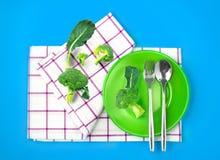 Τοπ άποψη του φρέσκου μπρόκολου στο πράσινο πιάτο και της πετσέτας δονούμενο σε ομο Στοκ εικόνες με δικαίωμα ελεύθερης χρήσης