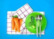Τοπ άποψη του φρέσκων μπρόκολου και των καρότων στο πράσινες πιάτο και την πετσέτα ο Στοκ εικόνα με δικαίωμα ελεύθερης χρήσης