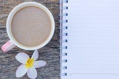 τοπ άποψη του φλυτζανιού καφέ με το λουλούδι Plumeria και το κενό σημειωματάριο Στοκ Εικόνες