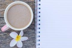 τοπ άποψη του φλυτζανιού καφέ με το λουλούδι Plumeria και το κενό σημειωματάριο Στοκ Φωτογραφία