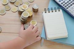 Τοπ άποψη του χεριού του ασιατικού παιδιού που βάζει ένα ασημένιο νόμισμα κοντά στο κενό βιβλίο σημειώσεων Στοκ Εικόνα