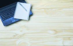 Τοπ άποψη του lap-top με το ανοικτό βιβλίο Lap-top με το βιβλίο ανοικτό στο ξύλο Στοκ εικόνες με δικαίωμα ελεύθερης χρήσης