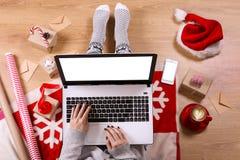 Τοπ άποψη του lap-top στα χέρια κοριτσιών ` s που κάθονται σε ένα ξύλινο πάτωμα με το φλιτζάνι του καφέ, τη διακόσμηση Χριστουγέν Στοκ φωτογραφία με δικαίωμα ελεύθερης χρήσης