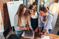 Τοπ άποψη τριών εύθυμων γυναικών σπουδαστών που εξετάζουν την κινητή τηλεφωνική οθόνη που στέκεται στην τάξη στοκ φωτογραφία