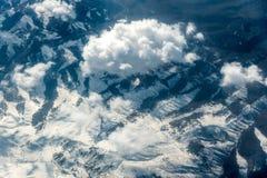 Τοπ άποψη των άσπρων σύννεφων μεταξύ των οποίων μπορείτε να δείτε τα υψηλά βουνά στοκ εικόνες