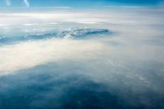 Τοπ άποψη των άσπρων σύννεφων μεταξύ των οποίων μπορείτε να δείτε τα υψηλά βουνά στοκ εικόνα με δικαίωμα ελεύθερης χρήσης