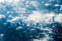 Τοπ άποψη των άσπρων σύννεφων μεταξύ των οποίων μπορείτε να δείτε τα υψηλά βουνά στοκ φωτογραφία