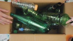 Τοπ άποψη των ανθρώπων στο γραφείο που βάζει τα πλαστικά μπουκάλια στην ανακύκλωση του δοχείου απόθεμα βίντεο