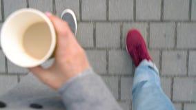 Τοπ άποψη των αρσενικών και θηλυκών ποδιών strolling κατά μήκος του πεζοδρομίου Καφές κατανάλωσης γυναικών φιλμ μικρού μήκους