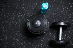 Τοπ άποψη των αλτήρων μετάλλων και ενός μπλε μπουκαλιού για το νερό, ουσία για τις αθλητικές ρουτίνες σε ένα σκοτεινό θολωμένο υπ Στοκ Εικόνες