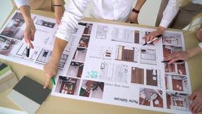 Τοπ άποψη των επιχειρηματιών που συναντιούνται γύρω από τον πίνακα αιθουσών συνεδριάσεων που συζητά τα αρχιτεκτονικά σχέδια για ν απόθεμα βίντεο