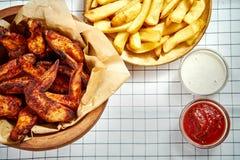 Τοπ άποψη των εύγευστων τηγανισμένων φτερών, των τηγανιτών πατατών και των σαλτσών κοτόπουλου στο τραπεζομάντιλο στοκ εικόνες