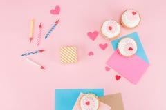 Τοπ άποψη των εύγευστων cupcakes, των ζωηρόχρωμων κεριών και των συμβόλων καρδιών στο ροζ Στοκ Φωτογραφίες