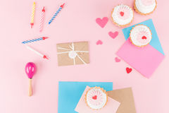 Τοπ άποψη των εύγευστων cupcakes, των ζωηρόχρωμων κεριών και των συμβόλων καρδιών στο ροζ Στοκ Εικόνα