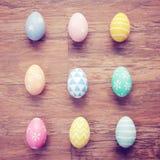 Τοπ άποψη των ζωηρόχρωμων αυγών Πάσχας στο ξύλινο υπόβαθρο στοκ εικόνες