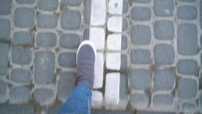 Τοπ άποψη των θηλυκών ποδιών στα γκρίζα πάνινα παπούτσια που περπατούν στο πεζοδρόμιο απόθεμα βίντεο