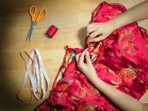 Τοπ άποψη των καλλιεργημένων θηλυκών χεριών που ράβουν το φόρεμα Cheongsam με τη βελόνα seamstress στον εργασιακό χώρο με το ράψι στοκ εικόνες
