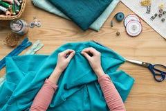 τοπ άποψη των καλλιεργημένων θηλυκών χεριών που ράβουν το ύφασμα με τη βελόνα Στοκ φωτογραφία με δικαίωμα ελεύθερης χρήσης