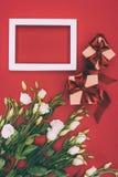 Τοπ άποψη των κιβωτίων δώρων, του κενού πλαισίου και των όμορφων λουλουδιών eustoma Στοκ Φωτογραφίες
