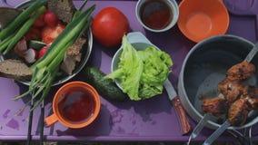 Τοπ άποψη των νέων που έχουν το γεύμα υπαίθριο Ψημένο στη σχάρα κρέας, φρέσκα λαχανικά απόθεμα βίντεο