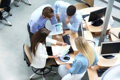 Τοπ άποψη των νέων σύγχρονων συναδέλφων στην έξυπνη περιστασιακή ένδυση που εργάζονται μαζί ενώ ξοδεύοντας χρόνος στο γραφείο στοκ εικόνα
