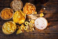 Τοπ άποψη των πιάτων με τα πρόχειρα φαγητά κοντά στο ποτήρι της μπύρας, σίτος, scatte Στοκ Εικόνα