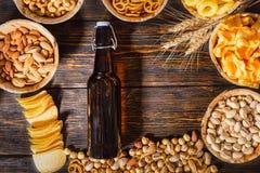 Τοπ άποψη των πιάτων με τα φυστίκια, τα καρύδια και άλλο νόστιμο sn μπύρας Στοκ φωτογραφία με δικαίωμα ελεύθερης χρήσης
