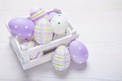 Τοπ άποψη των πορφυρών αυγών Πάσχας στο άσπρο καλάθι Πάσχα backgroun Στοκ Εικόνες