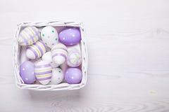 Τοπ άποψη των πορφυρών αυγών Πάσχας στο άσπρο καλάθι Πάσχα backgroun Στοκ Φωτογραφίες