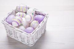 Τοπ άποψη των πορφυρών αυγών Πάσχας στο άσπρο καλάθι Πάσχα backgroun Στοκ φωτογραφία με δικαίωμα ελεύθερης χρήσης