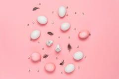 Τοπ άποψη των ρόδινων και άσπρων αυγών με τα λαγουδάκια, catkins και των φτερών στο ροζ Στοκ Εικόνες