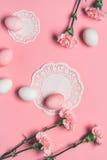 Τοπ άποψη των ρόδινων και άσπρων αυγών με τα λουλούδια και των πετσετών δαντελλών στο ροζ Στοκ Εικόνες